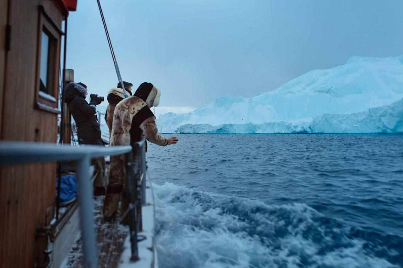 Tourists taking photos on an iceberg boat tour in Ilulissat in Greenland. By Rebecca Gustafsson