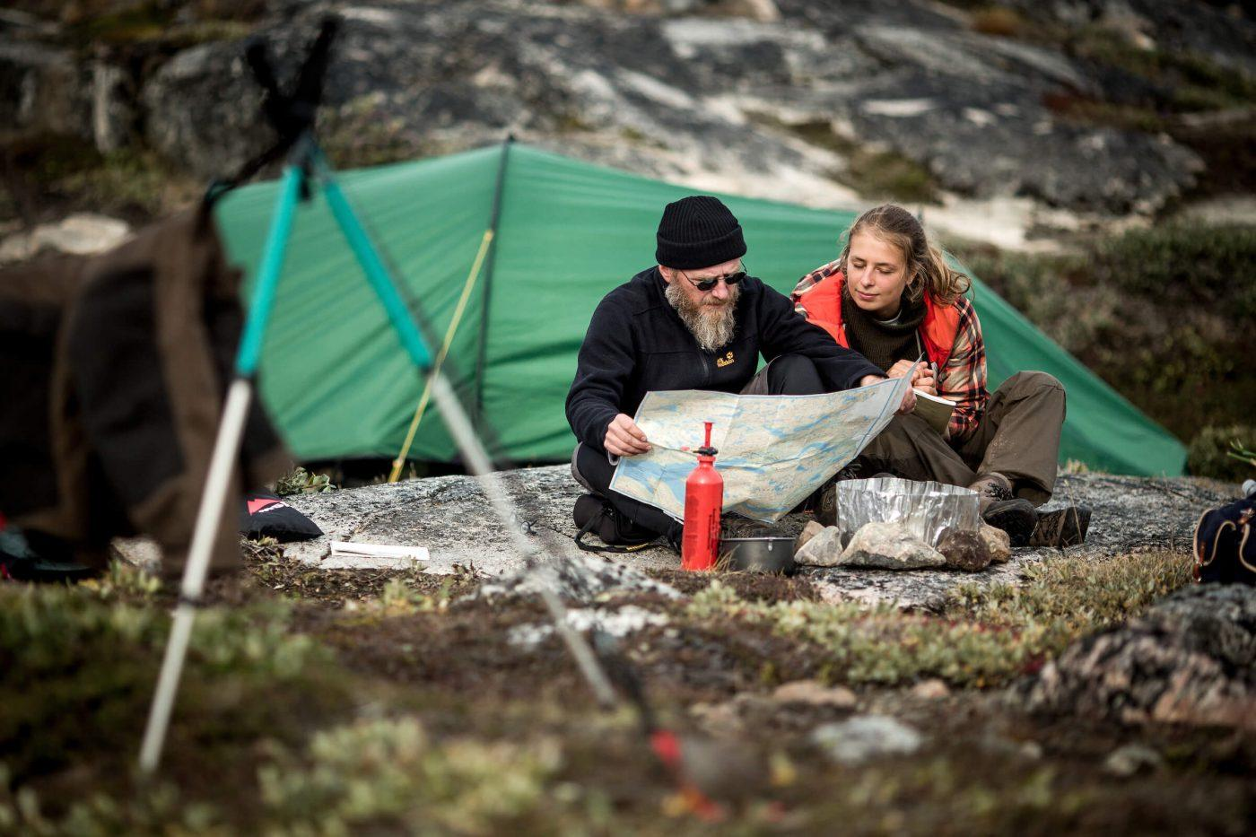 Two hikers at a campsite in Greenland near Ilulissat studying a map. By Mads Pihl