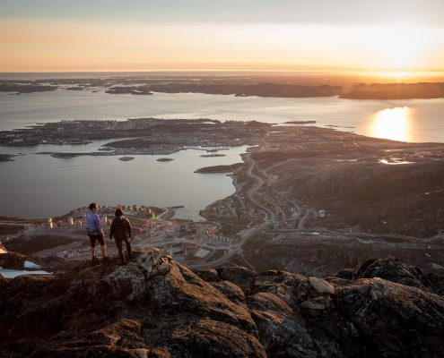 Two hikers overlooking Nuuk in the midnight sun from the peak of Ukkusissaq - Store Malene in Greenland