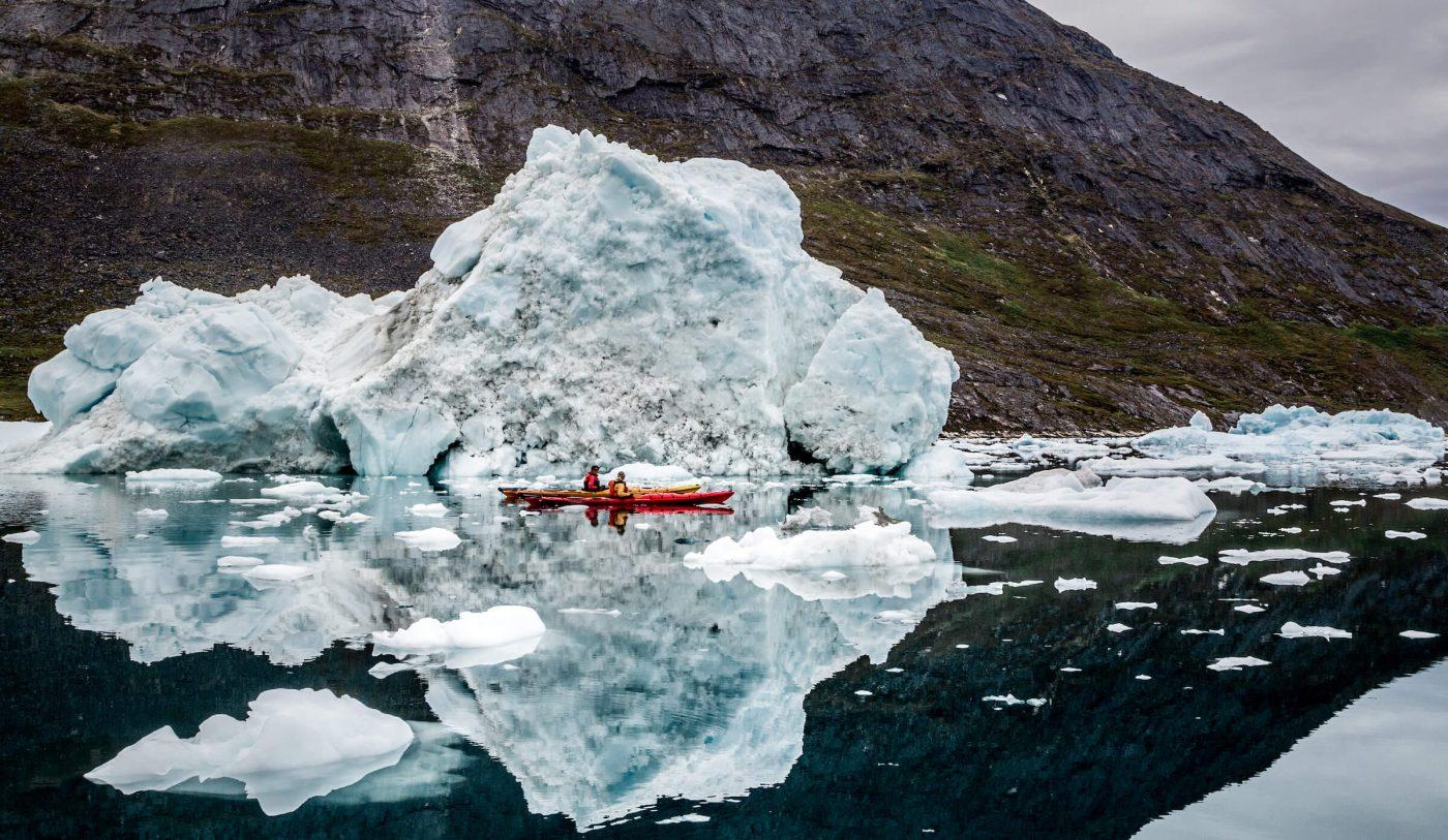 Two kayakers paddle around icebergs in Nuuk Fjord as a daytime adventure while staying at the Arctic Nomad Adventure Camp. By Raven Eye Photography
