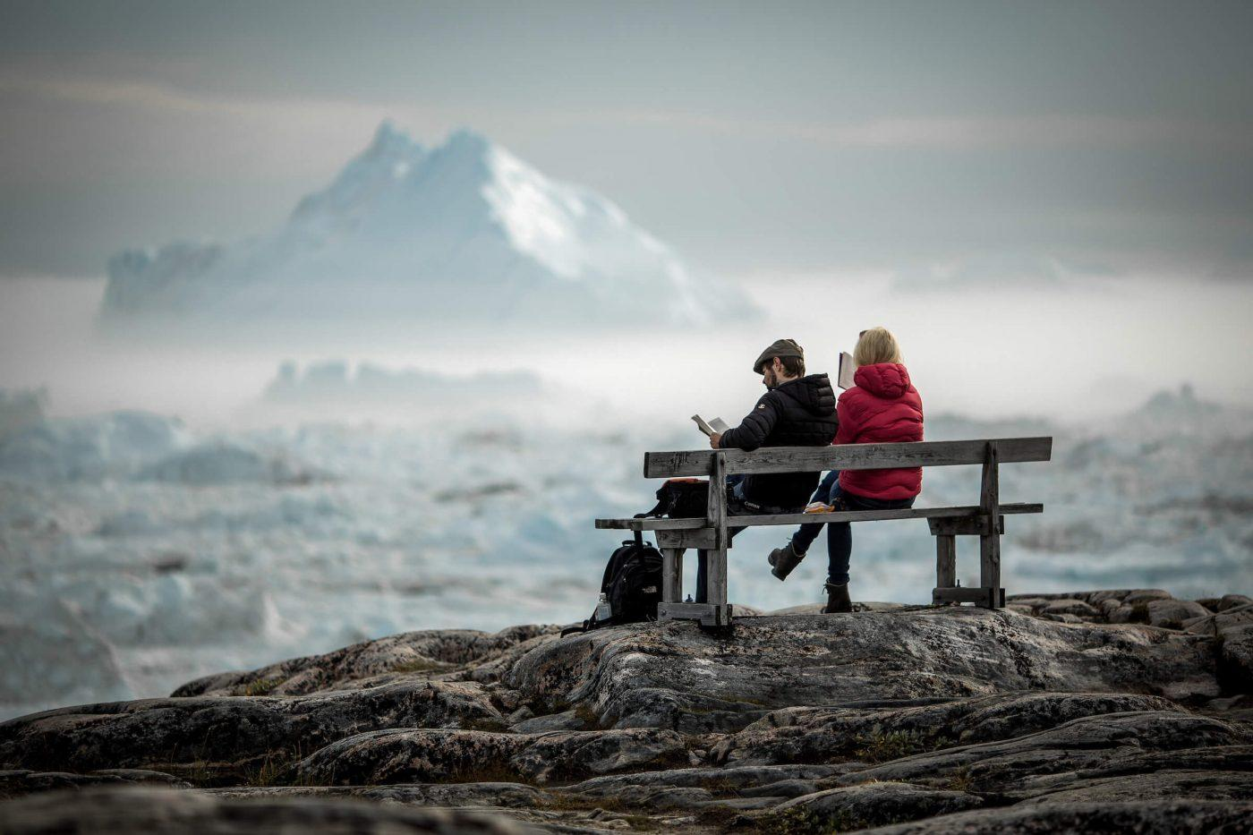 Two travelers reading on a bench overlooking icebergs in the Ilulissat ice fjord in Greenland. By Mads Pihl
