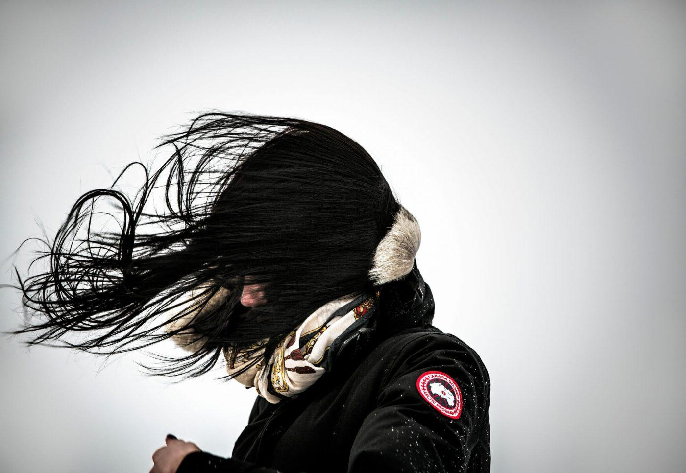 Woman with hair blowing in strong wind in Greenland, by Mads Pihl