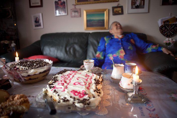 An elderly woman at a kaffemik laughing and enjoying herself. By Angu Motzfeldt