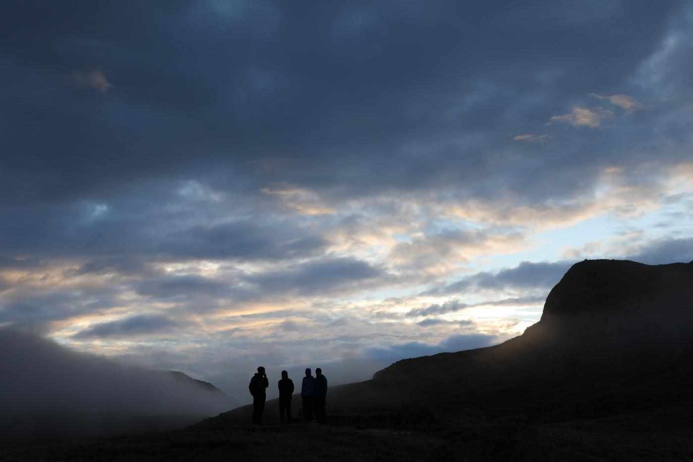 Hikers on mountain top with fog, sun and clouds. Photo by Morten Christensen - Visit Greenland