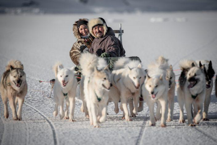 A Chinese traveler with her guide and dog musher on a sled near Ilulissat in Greenland. By Mads Pihl