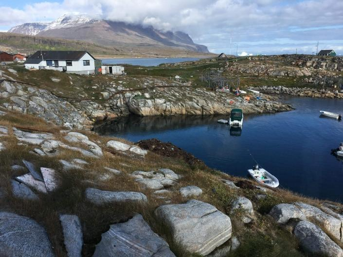 View over a little harbour in Qeqertarsuaq with large mountains in the background. Photo by Skansen - Your Home, Visit Greenland