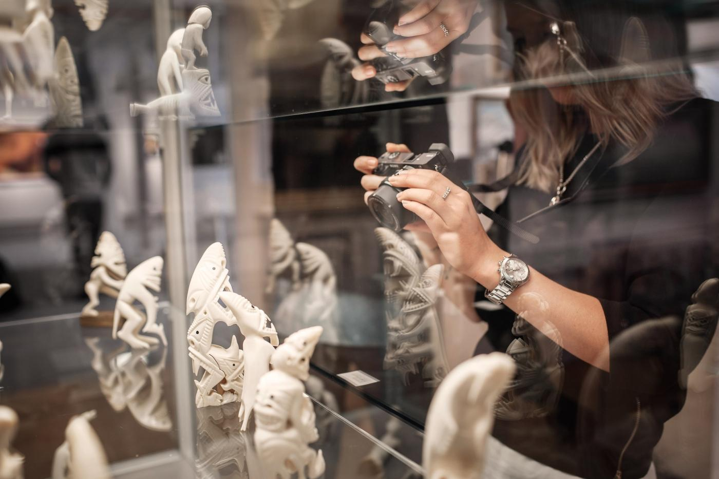 Woman taking a photo of some tupilaks in Nuuk Art Museum. Photo by Rebecca Gustafsson - Visit Greenland