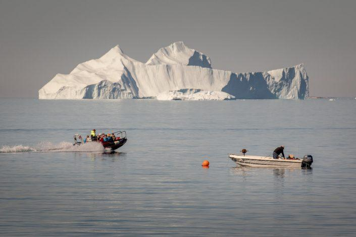 A tenderboat from MS Fram going past a fisherman at work in Upernavik in Greenland. Photo by Mads Pihl.