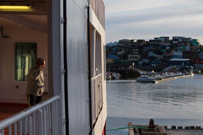 An elderly man talking on his cellphone while Sarfaq Ittuk was docked in Maniitsoq in Greenland. By Arctic Umiaq Line A/S