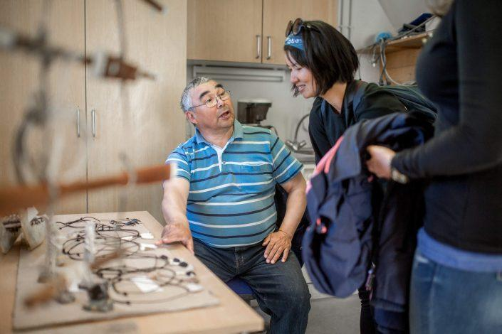 An MS Fram cruise guest talking to a local artist from Upernavik in Greenland. Photo by Mads Pihl.
