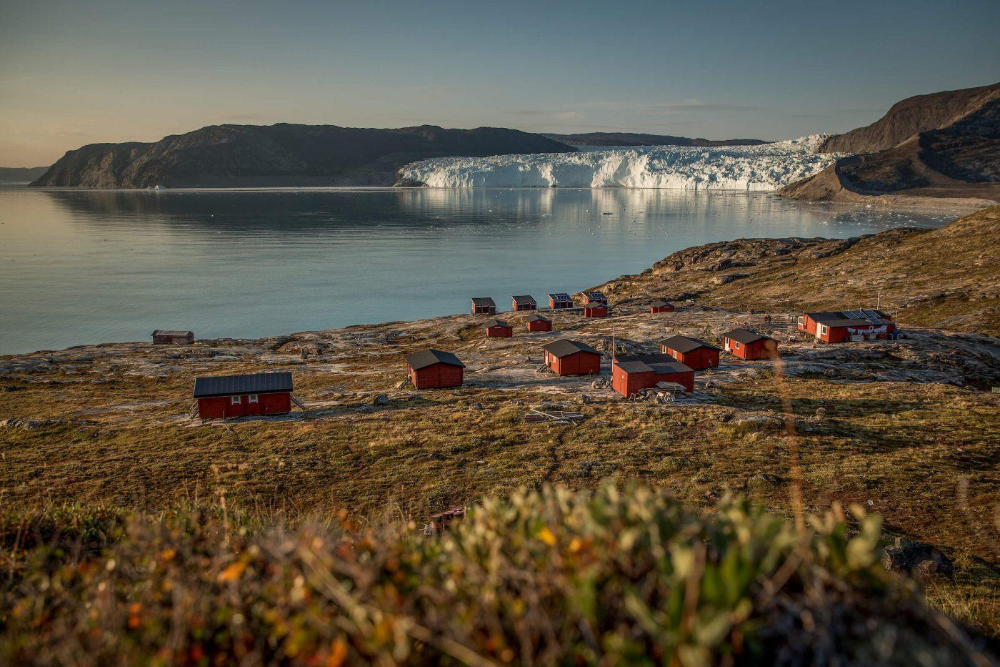 An overview of the Eqi Glacier Lodge camp with the glacier in the background in North Greenland. By Mads Pihl