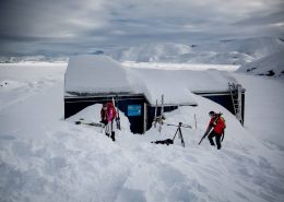 Backcountry skiers preapring fro a day in the landscape around the Travellodge Greenland hut in East Greenland. By Mads Pihl