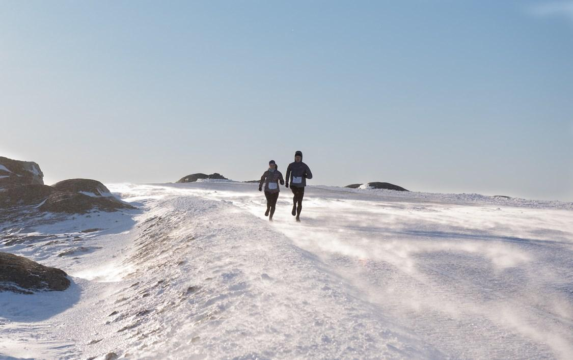 Two runners running in windy snow. By Bo Kristensen