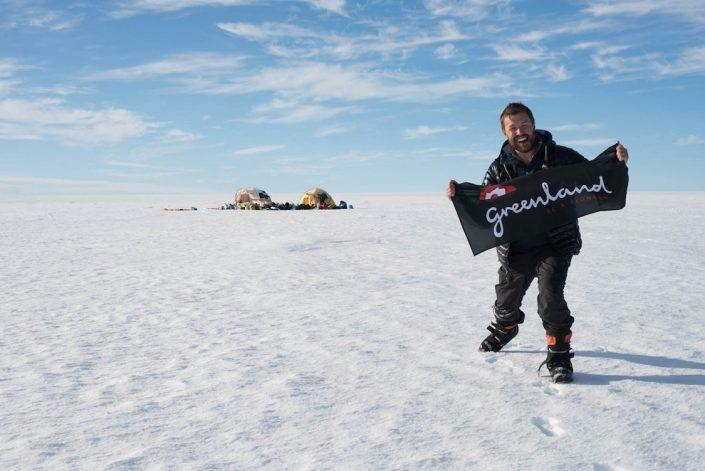 "The author on the East Greenland section of the inland ice with a ""Greenland, Be a Pioneer"" flag. By Malik Milfeldt"