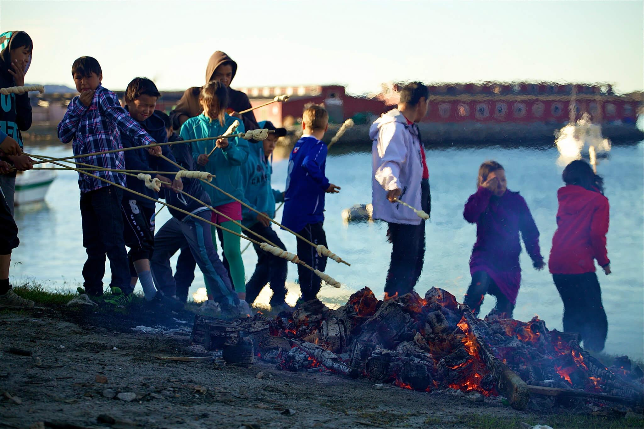 Kids making twist bread at bonfire in Aasiaat. Photo by Magssannguaq Qujaukitsoq.