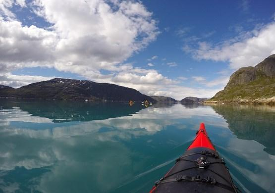 Kayak in mirror fjord. By Visit Greenland