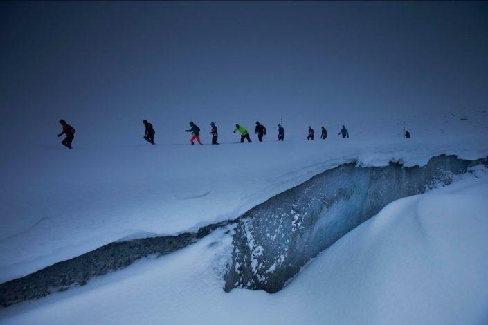 Polar Circle Marathon Runners Going through Snow. By Visit Greenland