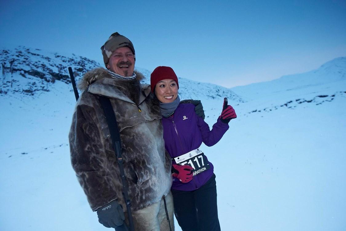 Happy man and woman posing at the polar circle marathon. By Visit Greenland