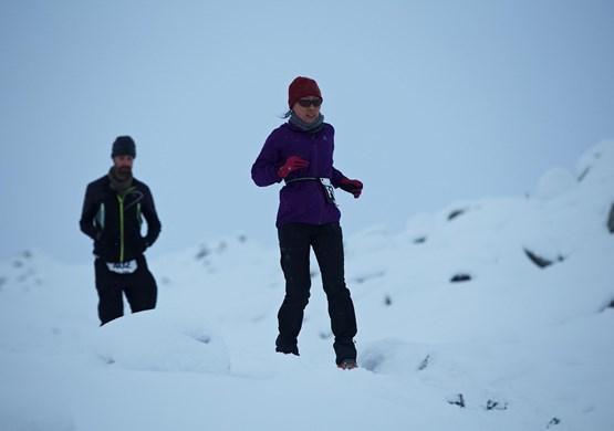 Woman running in snow at the Polar Circle Marathon. By Visit Greenland