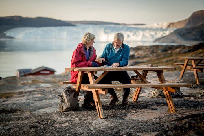 Two guests at Eqi Glacier Lodge in Greenland at a picnic table with the glacier in the background. By Mads Pihl