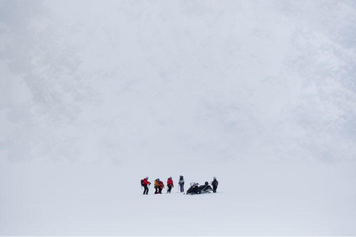 A group of skiers assembled at the bottom of a hill in East Greenland. Photo by Mads Pihl