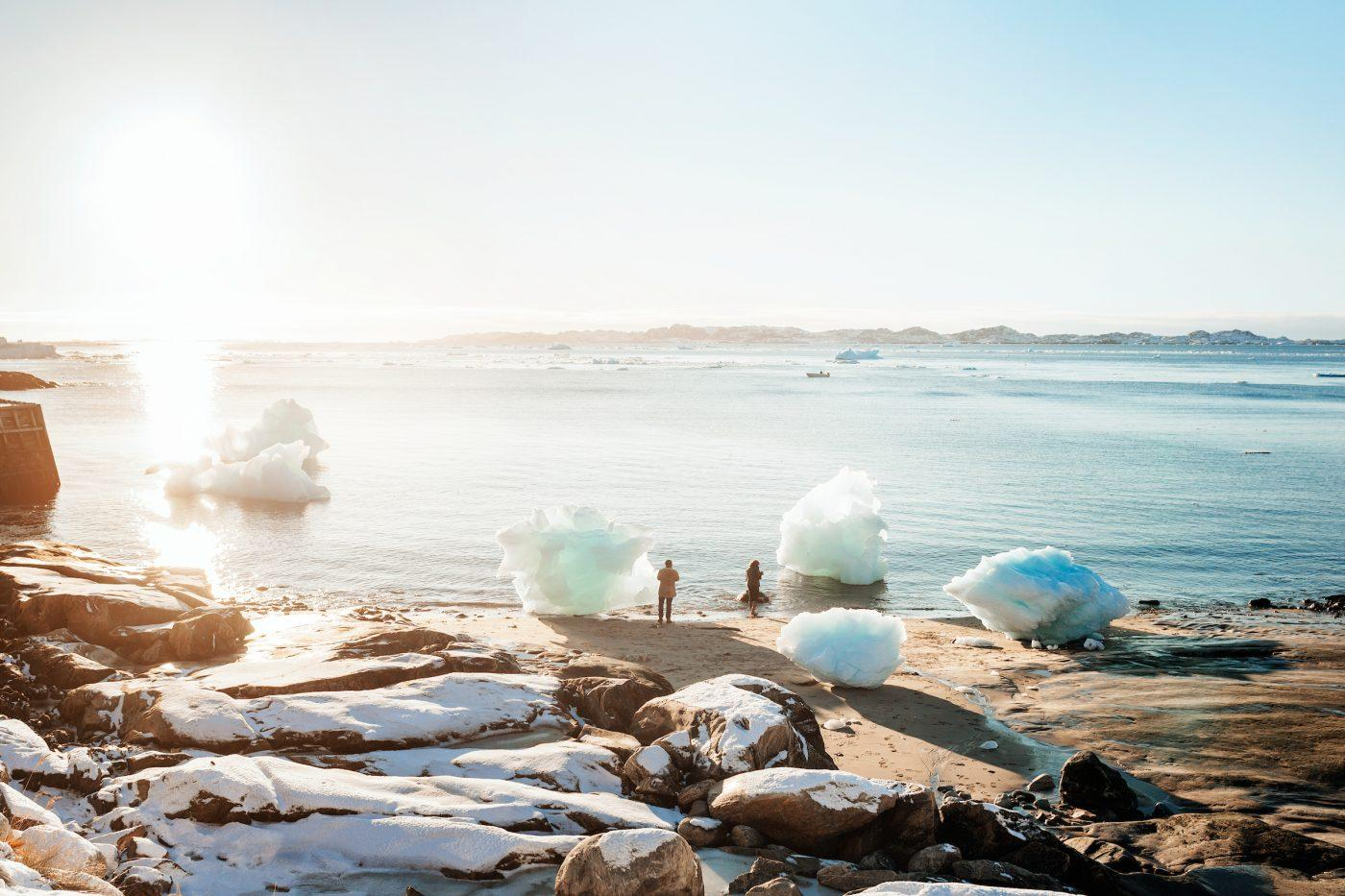 Two tourists on the beach in the colonial harbour of Nuuk in Greenland taking photos of washed up iceblocks in the sunset. Photo by Rebecca Gustafsson
