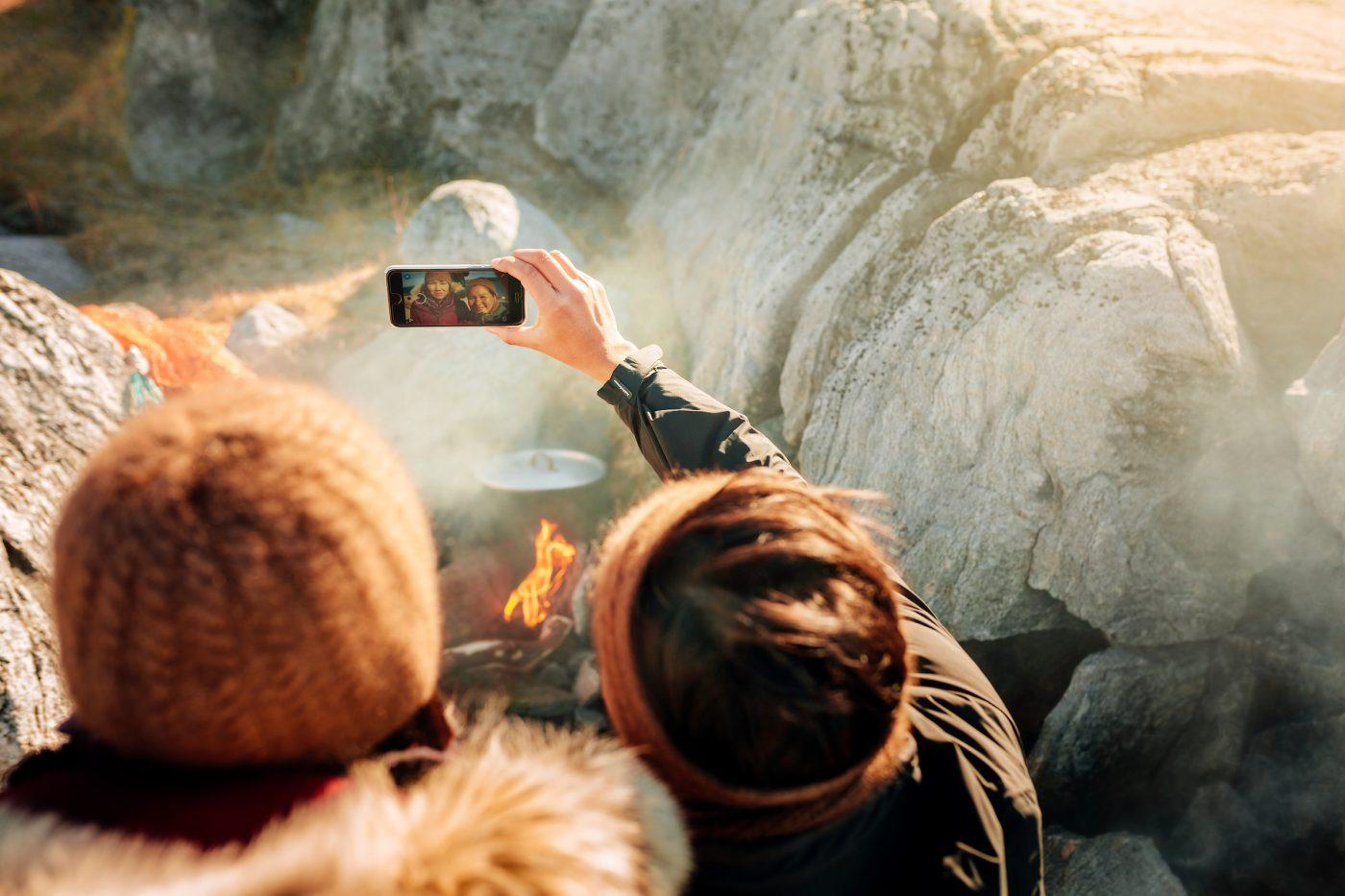 Two women taking a selfie by the fire on the beach in Nuuk in Greenland. Photo by Rebecca Gustafsson