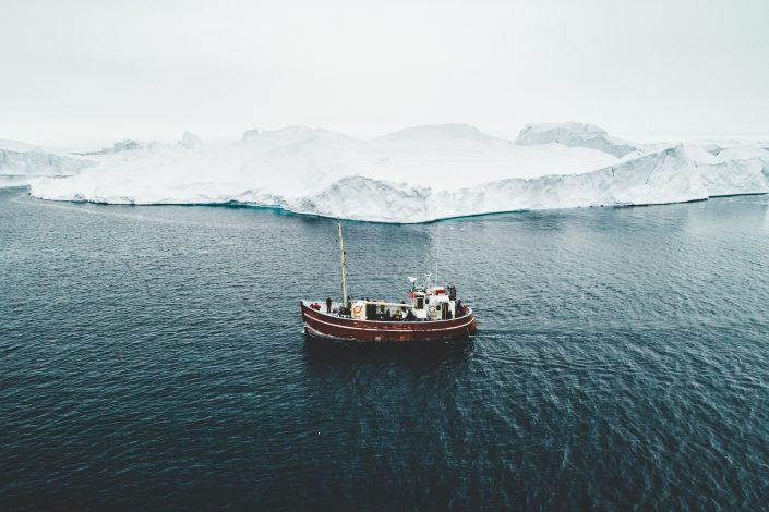 A Boat Tour in Ilulissat Icefjord with an old wooden boat. Photo by Benjamin Hardman