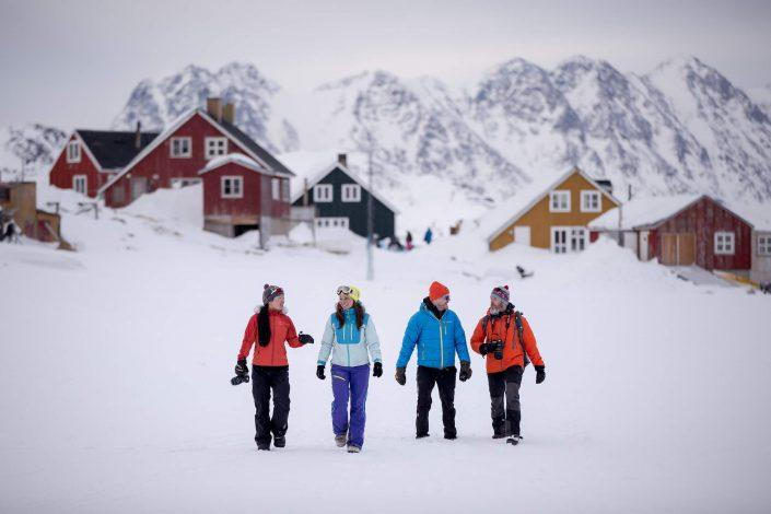 A group of travelers sightseeing by foot in Kulusuk, East Greenland. Photo by Mads Pihl