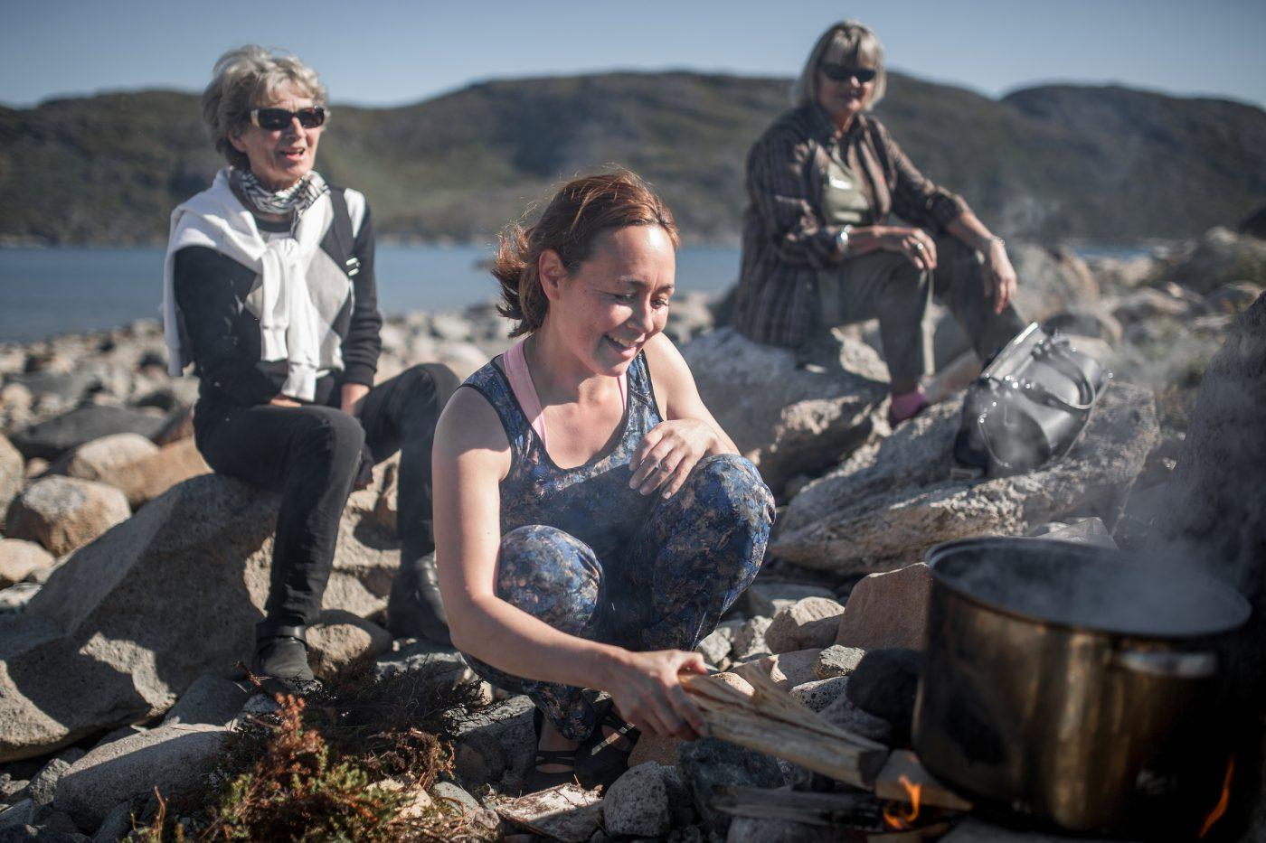 A young woman cooking on open fire in Narsaq in South Greenland. Photo by Mads Pihl