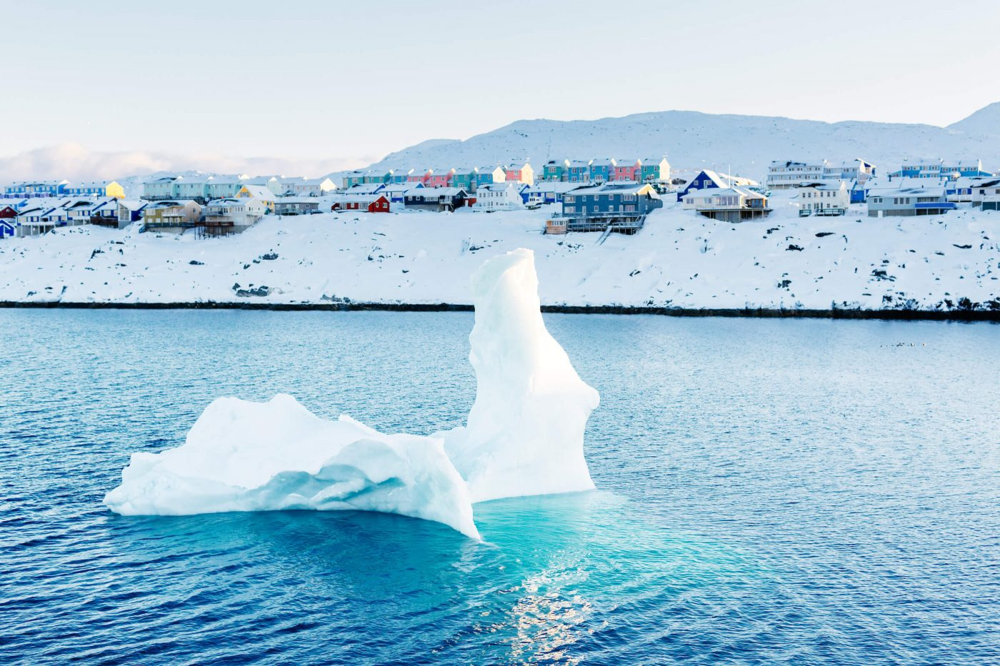 Small iceberg floating in the water in front of the houses of Nussuaq in Nuuk in Greenland