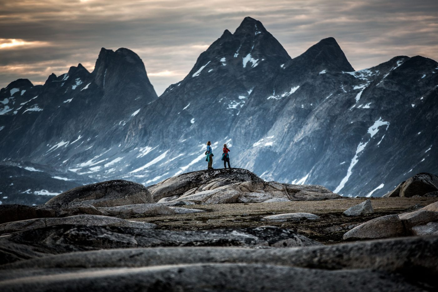 Two hikers at the top of a field with a mountain in the background. Photo by Mads Pihl