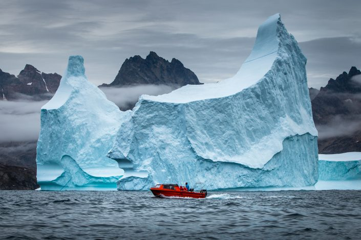 A ship sailing in front of a big iceberg. Photo by Mads Pihl