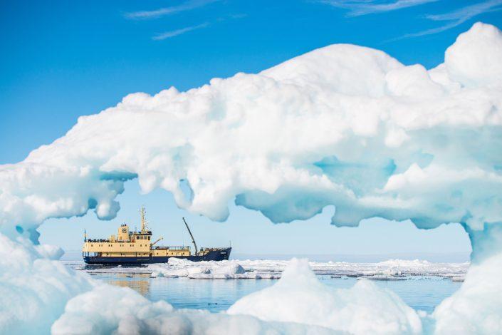 A Freya ship seen through a hole in an iceberg. Photo by Shannon Wild