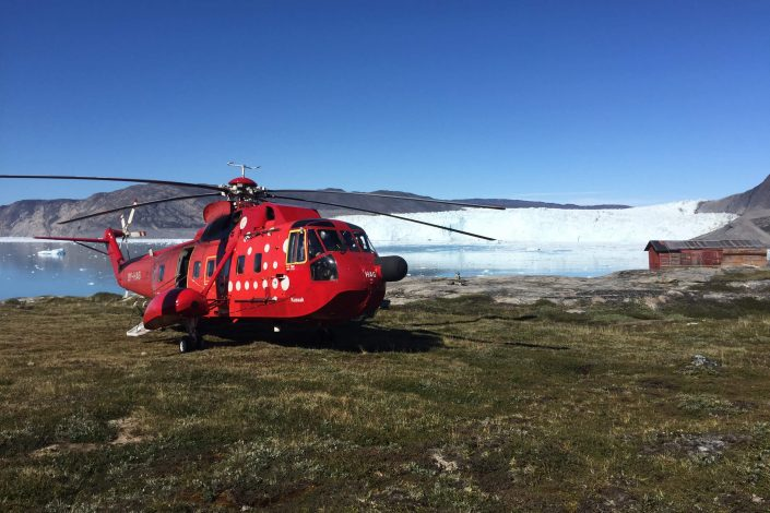Red helicopter about to take off close to the water. Photo by Arctic Nomad