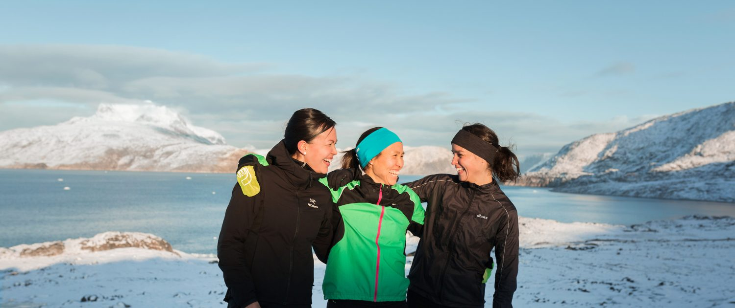 Three friends posing for a photo in running clothes in Nuuk in Greenland. Photo by Rebecca Gustafsson.