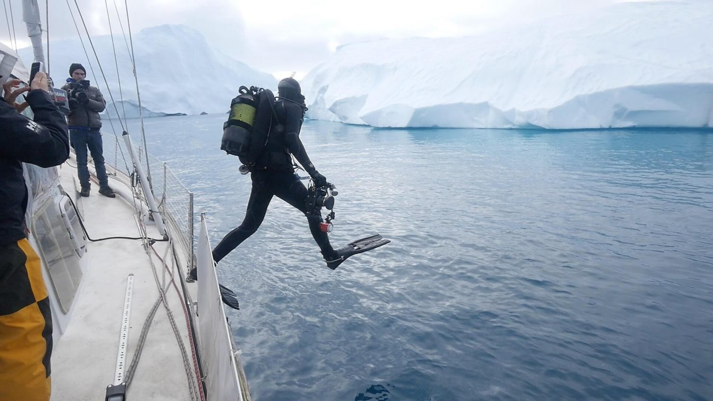 Diver Kingsley Griffin enters the -2 degree water of the Ilulissat icefjord
