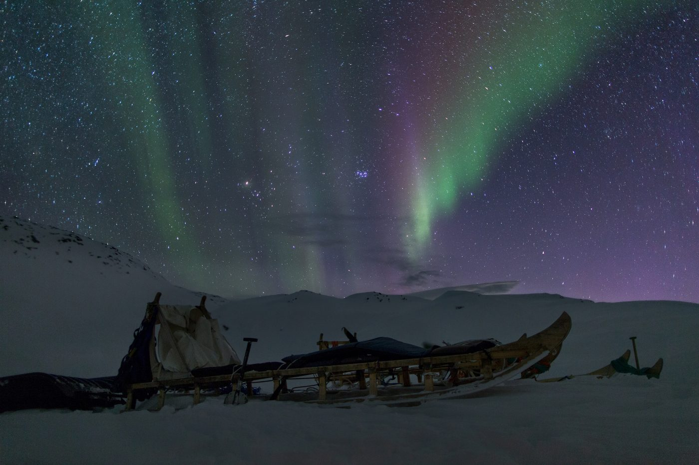Northern Lights over a typical East Greenland dog sled near the Travellodge Greenland hut at Sermilik in Greenland. Photo by Mads Pihl.