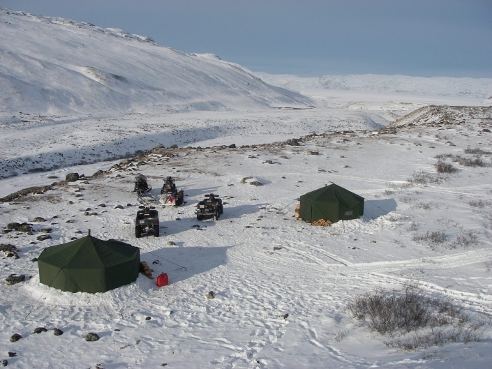 Winter camp in Kangerlussuaq with tents ATV and snowmobiles. Photo by North Safari Travel