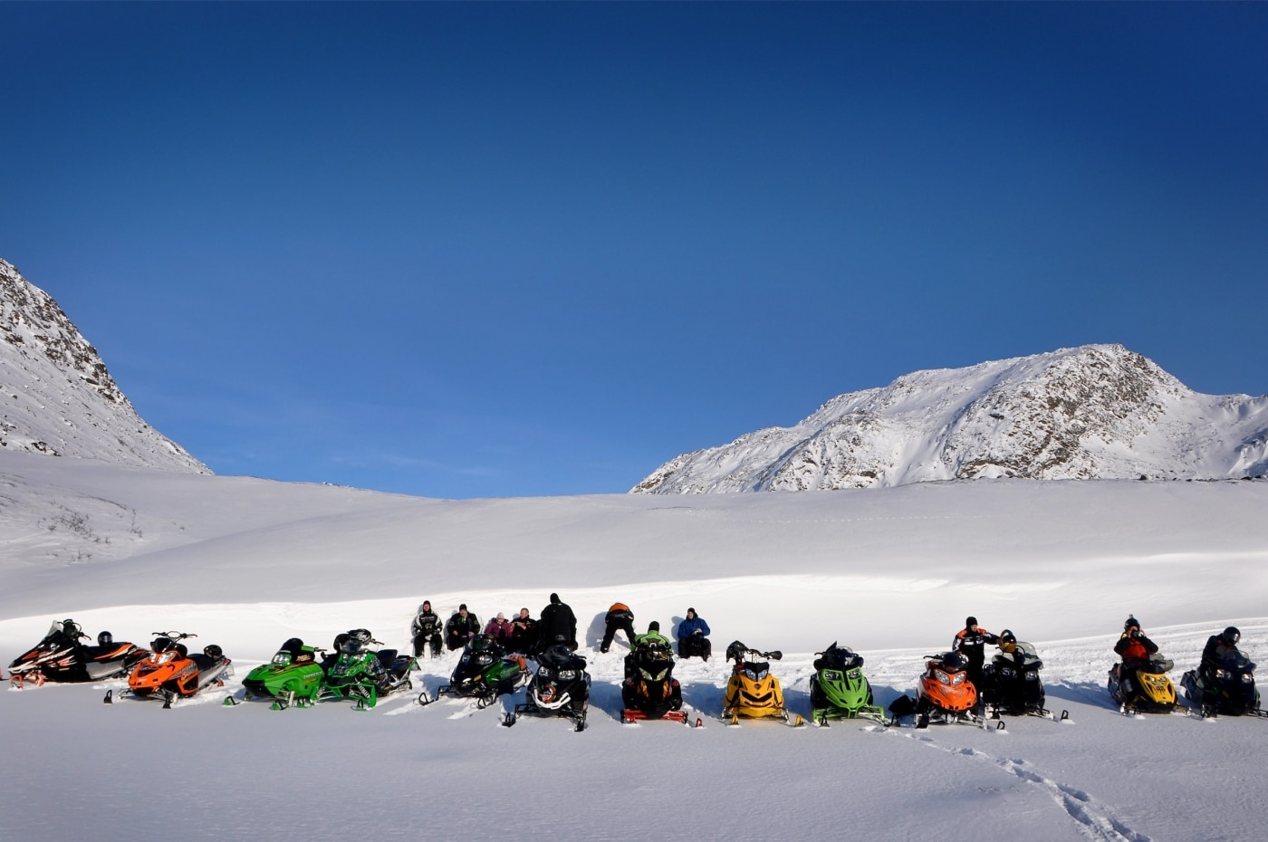 A group of snowmobilers enjoying the spring sun near Sisimiut in Greenland. Photo by Mads Pihl - Visit Greenland.