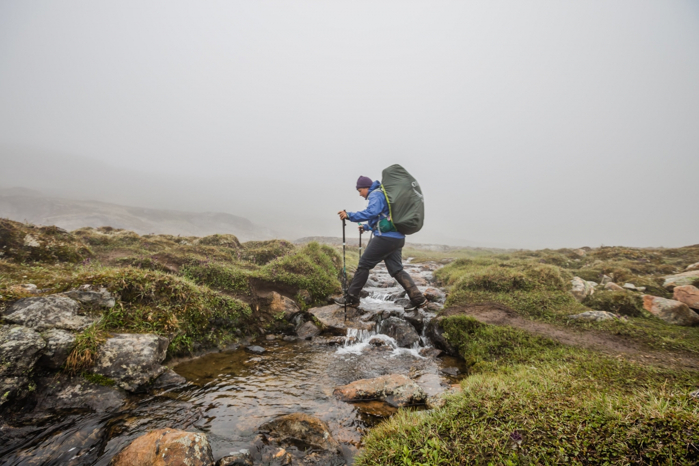 Female hiker crossing a small stream on the Arctic Circle Trail. Photo by Lina Stock.