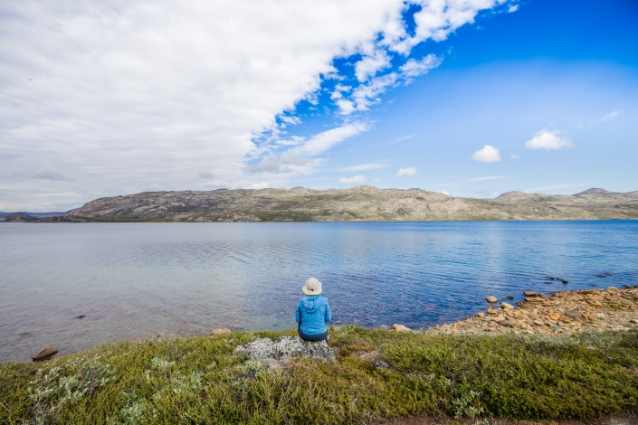 Female hiker taking a rest stop on the shores of Amitsorsuaq Lake along the Arctic Circle Trail. Photo by Lina Stock