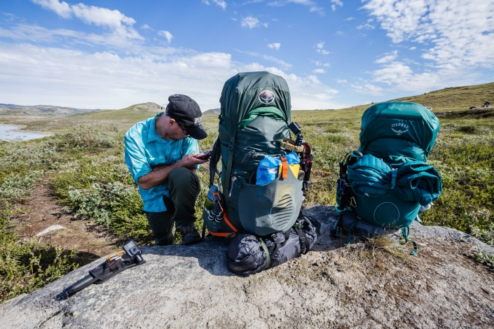 Hiker making a rest stop and adding coordinates to a GPS unit on the Arctic Circle Trail. Photo by Lina Stock.