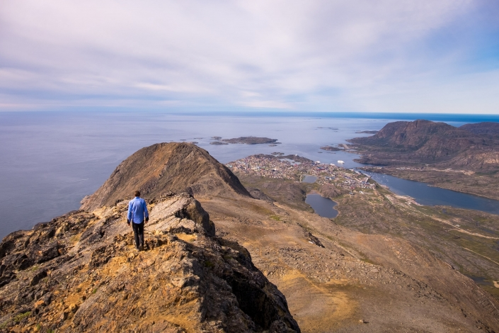 Hiker on top of Nasaasaaq with Sisimiut below - Arctic Circle Trail option. Photo by Lisa Germany.