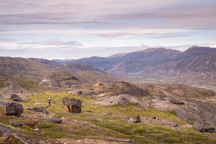 Hiker passing large boulders with Itinneq Valley in the distance - Day 4 of Arctic Circle Trail. Photo by Lisa Germany.