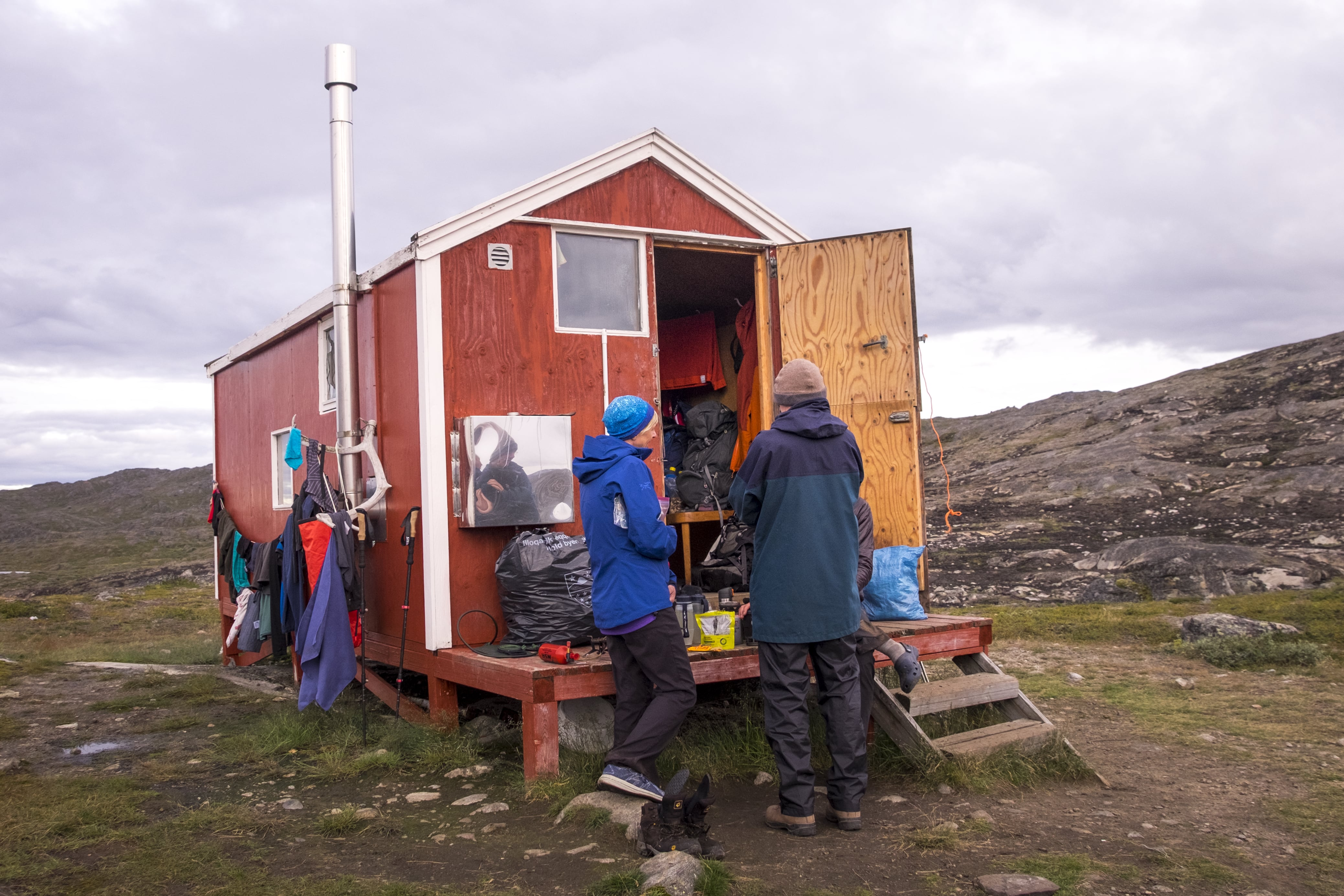 Hikers preparing food on the patio of Ikkattooq Hut - Day 3 of Arctic Circle Trail. Photo by Lisa Germany