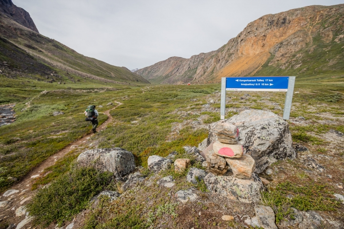 Male hiker passes cairn trail marker and hut sign while approaching Nerumaq Hut on the Arctic Circle Trail. Photo by Lina Stock.