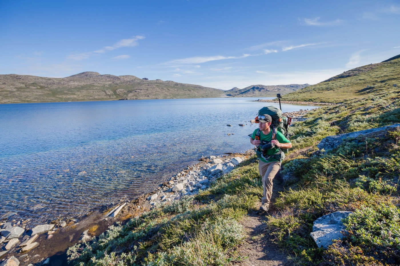 Male hiker walking on a path next to a lake on the Arctic Circle Trail. Photo by Lina Stock.