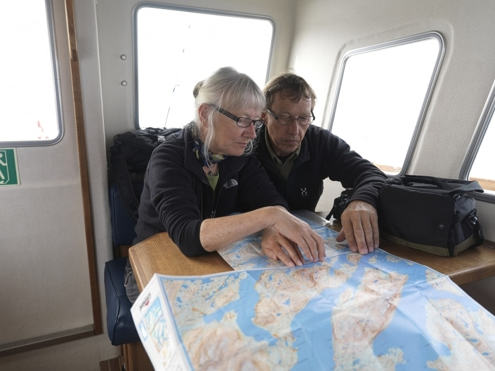 Travelers on a boat ride in South Greenland study a map of the hiking trails and fjords in the region. Photo by David Trood.