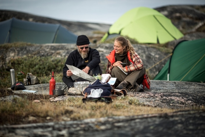 Two hikers at a campsite in Ilulissat in Greenland looking at a topo map. Photo by Mads Pihl - Visit Greenland.